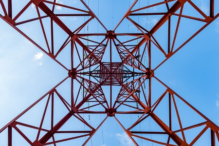 Bottom view of power pylons with blue sky on background.