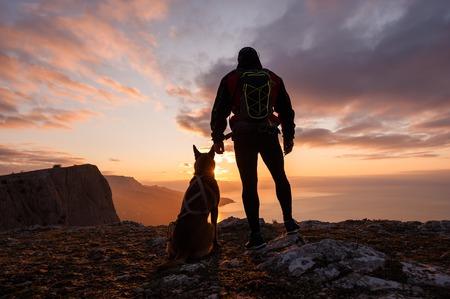 Silueta del hombre joven con su perro al amanecer con el mar y la montaña en el fondo. Foto de archivo - 84042345