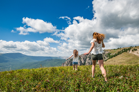Two girls running on the meadow with mountains and cloudscape on background. Zdjęcie Seryjne