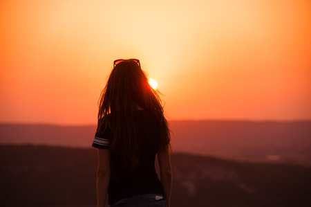 Girl silhouette at sunset against the sun