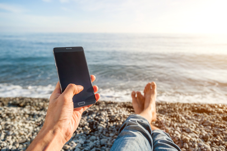 Guy on the beach with phone