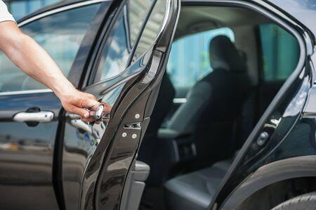 Close up man opens cars door.