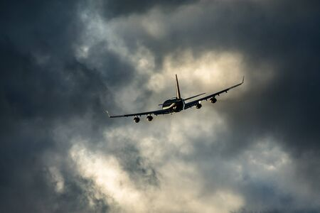 Airplane take off at sunset with clouds