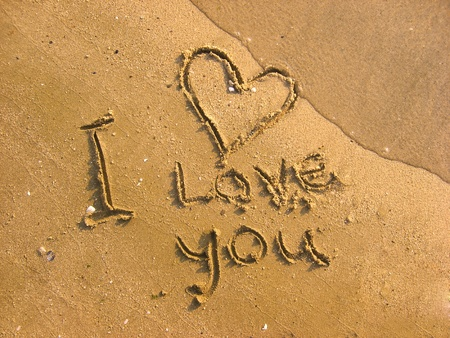 I love you written on the beach and one wavelet erasing it photo