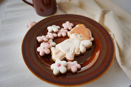 Ginger cookies soft colors flower and angel shape on brown ceramic plate