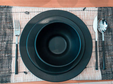 Black ceramic dishes and cups set up table