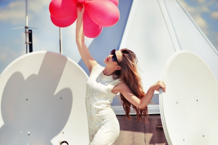 etalon: Beautiful woman in elegant dress on the top of modern building with balloons