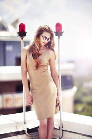 etalon: Beautiful woman in elegant dress on the top of modern building