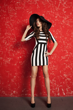 positiv: Beautiful young woman with long curly hair in black hat and striped dress on red background.