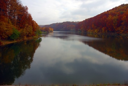 Fall forest landscape with red and yellow maple foliage and lake photo