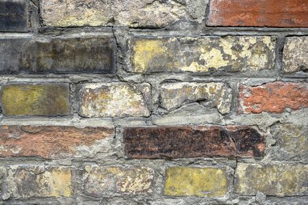 Fragment of an old brick wall. The texture of the brickwork of different colors. Close-up. Selective focus.