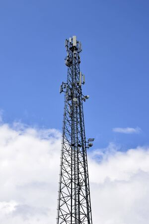 Cell tower against blue sky with clouds. A cell site or tower with antennae and telecommunications equipment is part of cellular network. Wireless communication. Moldova. Selective focus. Copy space. Reklamní fotografie