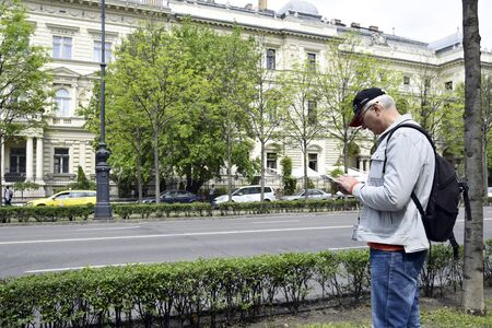 Budapest, Hungary-may 2019: vacation, vacation, tour: a tourist with a backpack, being on Andrassy Avenue, lays a walking route in a mobile phone.  Man traveler in the historic center of the city.