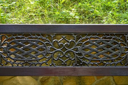Celosía de calado forjado en un marco de madera en el fondo de un muro de piedra salvaje y vegetación verde. Un fragmento de un banco de calle ubicado en un acogedor parque. De cerca. Enfoque selectivo. Copie el espacio. Foto de archivo