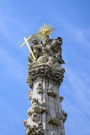Fragment of Holy Trinity Column (plague column) in Budapest against blue sky with clouds. Plague Column located on Castle hill in middle of Trinity Square. Column was built to celebrate end of plague.