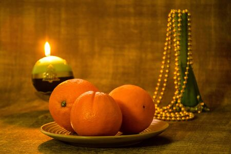 Ð¡hristmas and New Year composition: three oranges on a ceramic plate, a green glass vase with Christmas beads and a burning Christmas candle on a dark background. Close-up. Selective focus. Copy space
