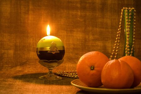 Ñhristmas and New Year composition: three oranges on a ceramic plate, a green glass vase with Christmas beads and a burning Christmas candle on a dark background. Close-up. Selective focus. Copy space Zdjęcie Seryjne