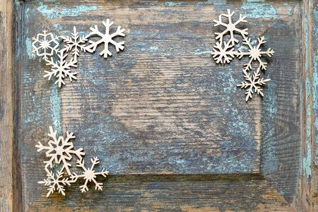 Christmas decoration, New Years toys. Wooden snowflakes laid out on an old wooden surface. Top view. Selective focus. Copy space. Imagens