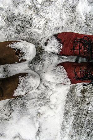 Legs Man and woman in warm winter shoes standing in the snow next to each other. Close-up feet of couple stand on the snow on a winter day. Stock Photo