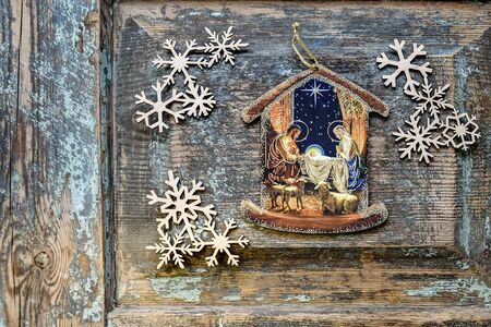 Christmas decoration: Nativity scene image and Wooden snowflakes laid on an old wooden surface. Top view. Selective focus. Copy space. Imagens