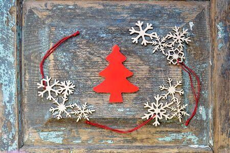 Decorazioni natalizie, giocattoli di Capodanno: albero di Natale rosso tagliato di cartone e fiocchi di neve in legno con corde rosse disposte su una vecchia superficie di legno. Vista dall'alto. Messa a fuoco selettiva. Copia spazio.