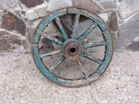 An old wooden cartwheel with a broken spoke. Cracked wooden elements painted with blue paint. Leaning against a stone wall. Close-up. Selective focus. Copy space. Stock Photo