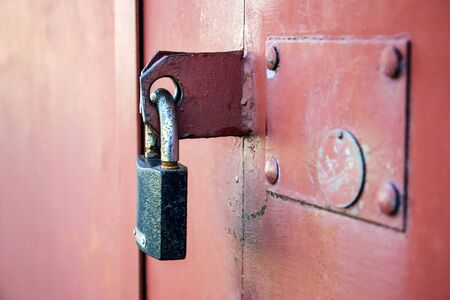 Small padlock on a red metal door. Close-up. Selective focus. Copy space.