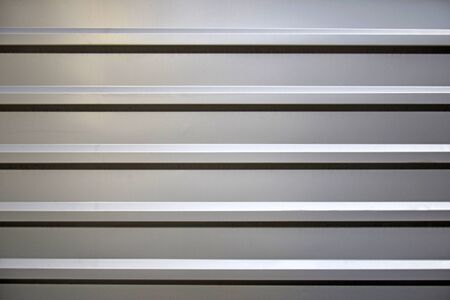 Profiled galvanized sheet with horizontal stripes. Partial lighting from above. Close-up. Selective focus. Copy space.