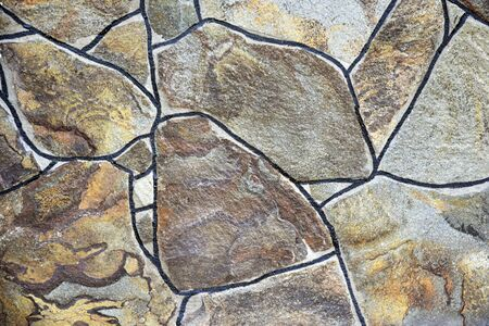 Wall covered with tiles in the form of wild stone. Close-up. Selective focus. Copy space.