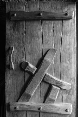 Oak wooden door made using old technology. Lateral natural light. Rustic style. Black and white vertical image. Close-up. Selective focus. Copy space. 스톡 콘텐츠