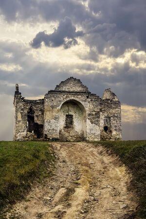 Ruines d'une ancienne église chrétienne sur fond de ciel nuageux. La route menant à l'ancien temple délabré. Espace de copie.