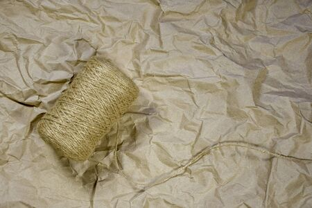 Coil of Hemp Twine on crumpled wrapping paper. Top view. Background, texture. Side lighting. Copy space.