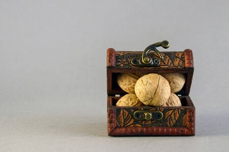 Small chest full of walnuts on gray background. Close-up. Selective focus. Copy space.