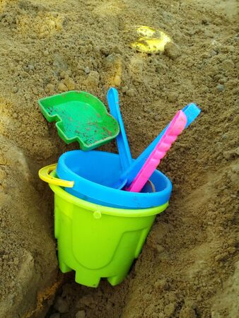 Colorful ñhildrens toys are forgotten in the sandbox. Plastic tools: shovel and pail. Close-up.