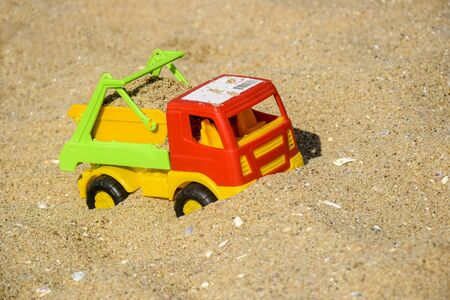Childrens toy car, colorful plastic lorry on beach sand. Summer sea vacation with children. Close-up. Selective focus. Copy space.