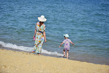 Woman with child walks along seashore on summer sunny day. Mother and baby, family beach vacation. Back view.