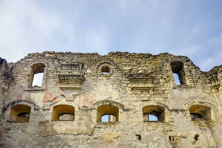Ruins of an ancient synagogue against the blue sky. Texture of old dilapidated masonry with arched windows. Moss-covered stones. Rashkov, Moldova. Selective focus.