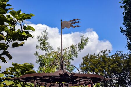 Metal wrought iron gazebo with flag developing on the roof. View against blue sky with clouds framed by green trees. Selective focus. Copy space. Close-up.