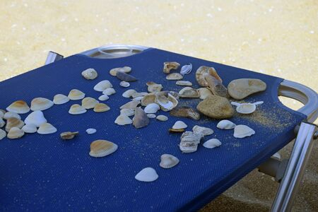 Sea shells and stones are laid out by children on blue deck chair with an aluminum frame. Childrens games on the beach. Selective focus. Copy space. Close-up. Banco de Imagens