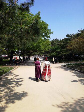 Korean women dressed in Hanbok - Korean traditional dress, walking along Seoul Street, South Korea. Tourism, travel.