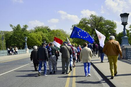BUDAPEST, HUNGARY - MAY 2019: Peaceful procession of people with flags on the main street. Demonstration in the city center. Selective focus.