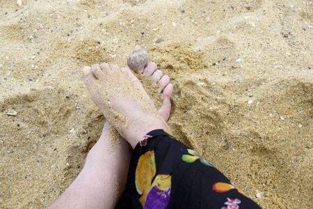 Summer and beach concept - woman and man feet together on sea sand. Romantic vacation couple of lovers or friends on beach. Top down view of female and male feets.