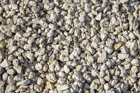 Limestone rubble. Construction material. Side lighting. Natural background. Selective focus. Close-up. Copy space.