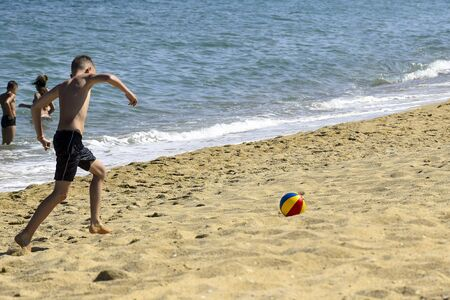 Boy plays with a ball on the seashore. Beach outdoor activities. Sports for health. Close-up. Selective focus. Copy space.