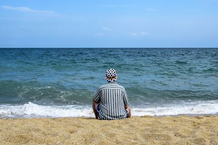 Man sits on the seashore and relaxes. Looks into the boundless blue distance. Vacation, beach vacation. Dressed in striped shirt and panama hat with soccer balls. Selective focus. Copy space.  Banco de Imagens