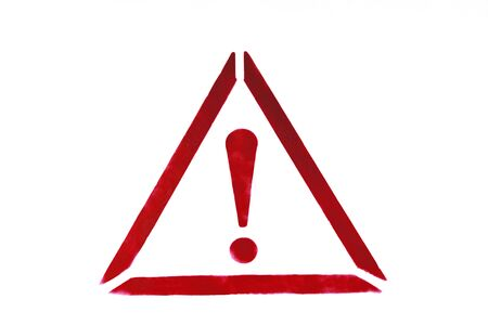 Exclamation mark in triangle drawn by red paint on white wall. Warning sign to prevent potential problems traffic accident. Close-up. Banco de Imagens