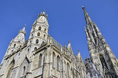 Vienna, Austria, may 2019: Details of the roof and tower of the Stephansdom -St Stephens church view against blue sky, one of the main tourist destination of Vienna.