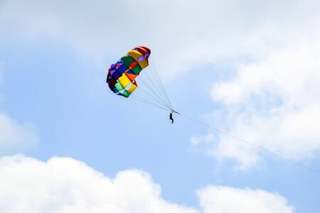 Multi-colored parachute with man soars in the blue sky between white clouds. Active beach vacation. Outdoor adventure. Close-up. Selective focus. Copy space.  Banco de Imagens