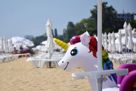 Summer holiday, beach vacation. Childrens inflatable colorful toy unicorn on background of beach umbrellas. Close-up. Selective focus. Banco de Imagens