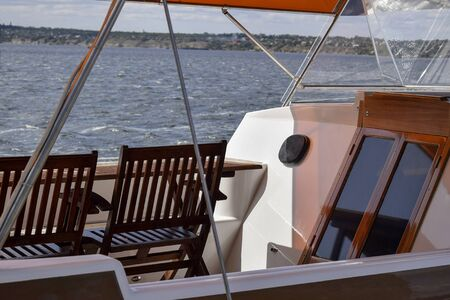 Recreation area on a pleasure yacht. Wooden table with chairs under sun awning. River View. Close-up. Selective focus.